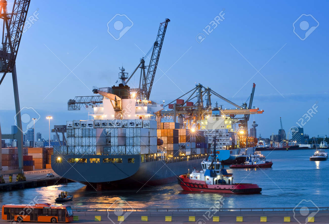 Several tugs and support vessels, assisting a huge container ship to moor off at the quay in the Rotterdam Harbor. A customs vehicle and crew bus are standing by to escort the crew through customs and to clear the cargo at dusk Stock Photo - 4880938