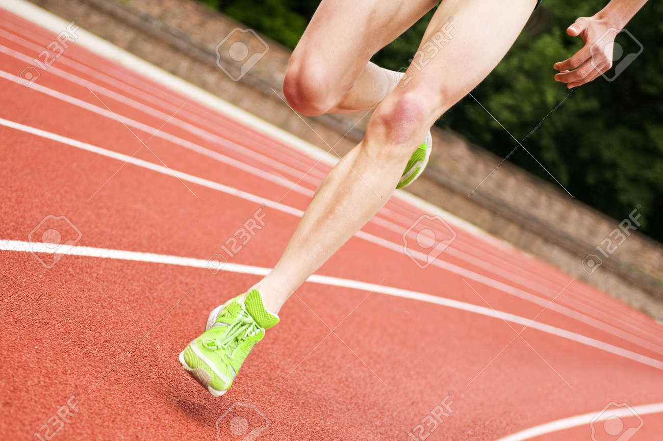 Legs and shoes of a long distance runner on an oval track - 5376174