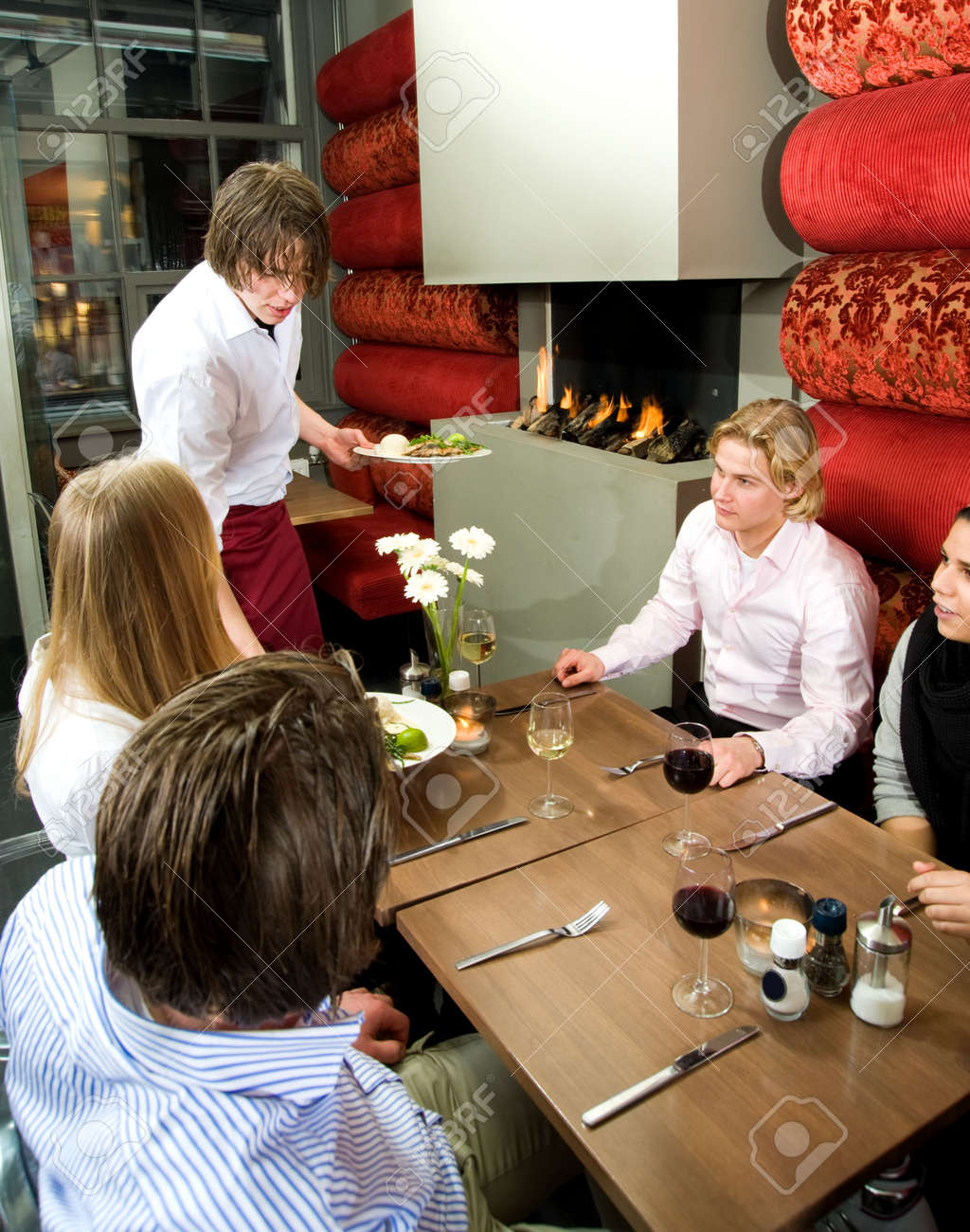 Waiter serving meals in a restaurant to a group of friends having dinner Stock Photo - 6485045