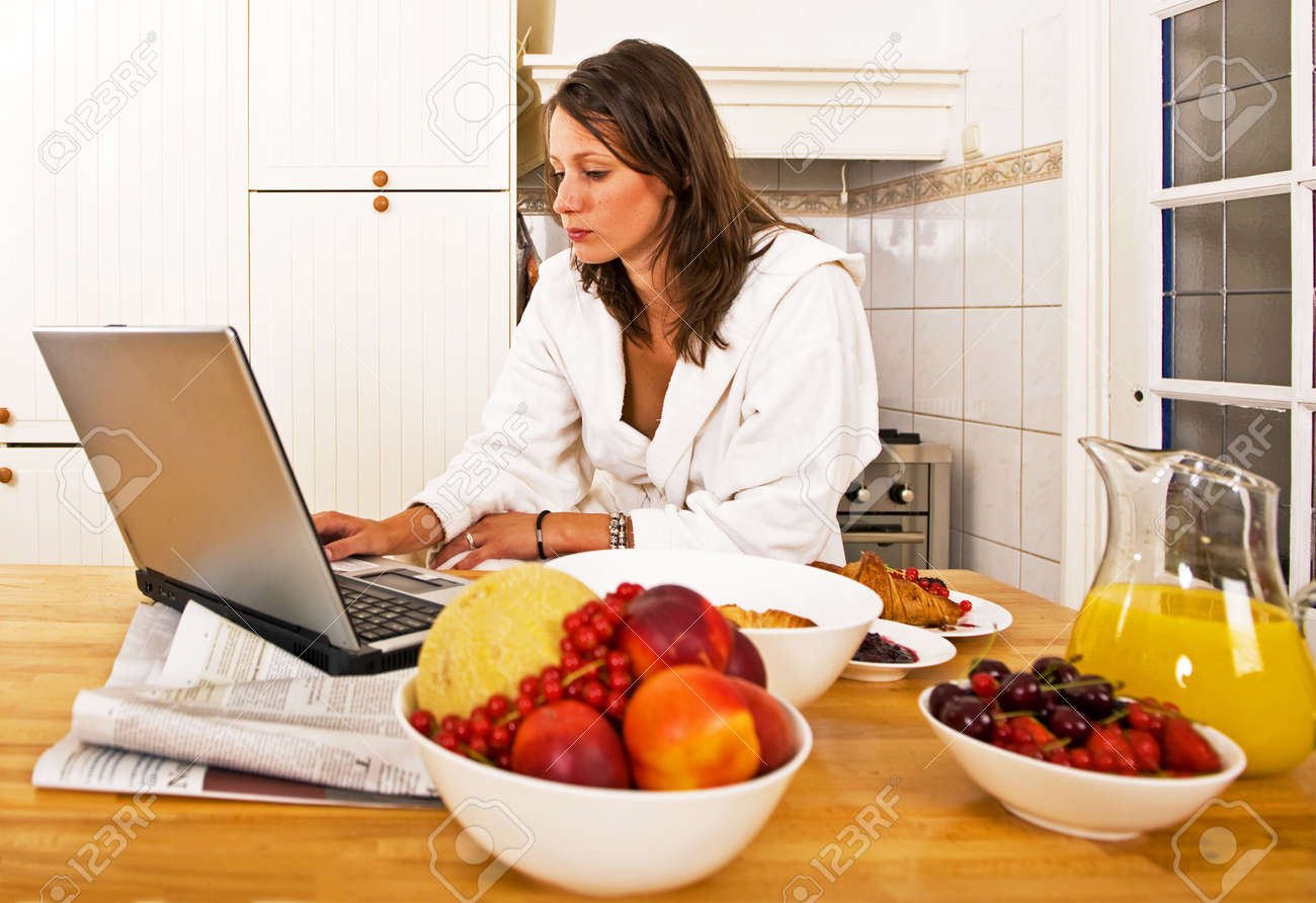 Young woman, catching up with the day's events on her laptop whilst drinking a glass of orange jus Stock Photo - 6492667