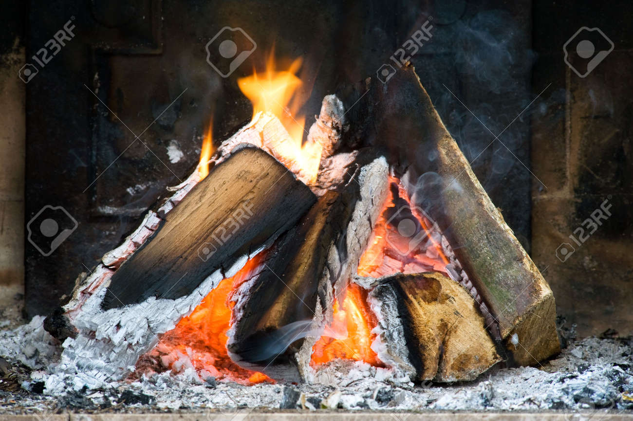 Several logs burning in a small fireplace surrounded by ashes, smoke and flames Stock Photo - 6492670