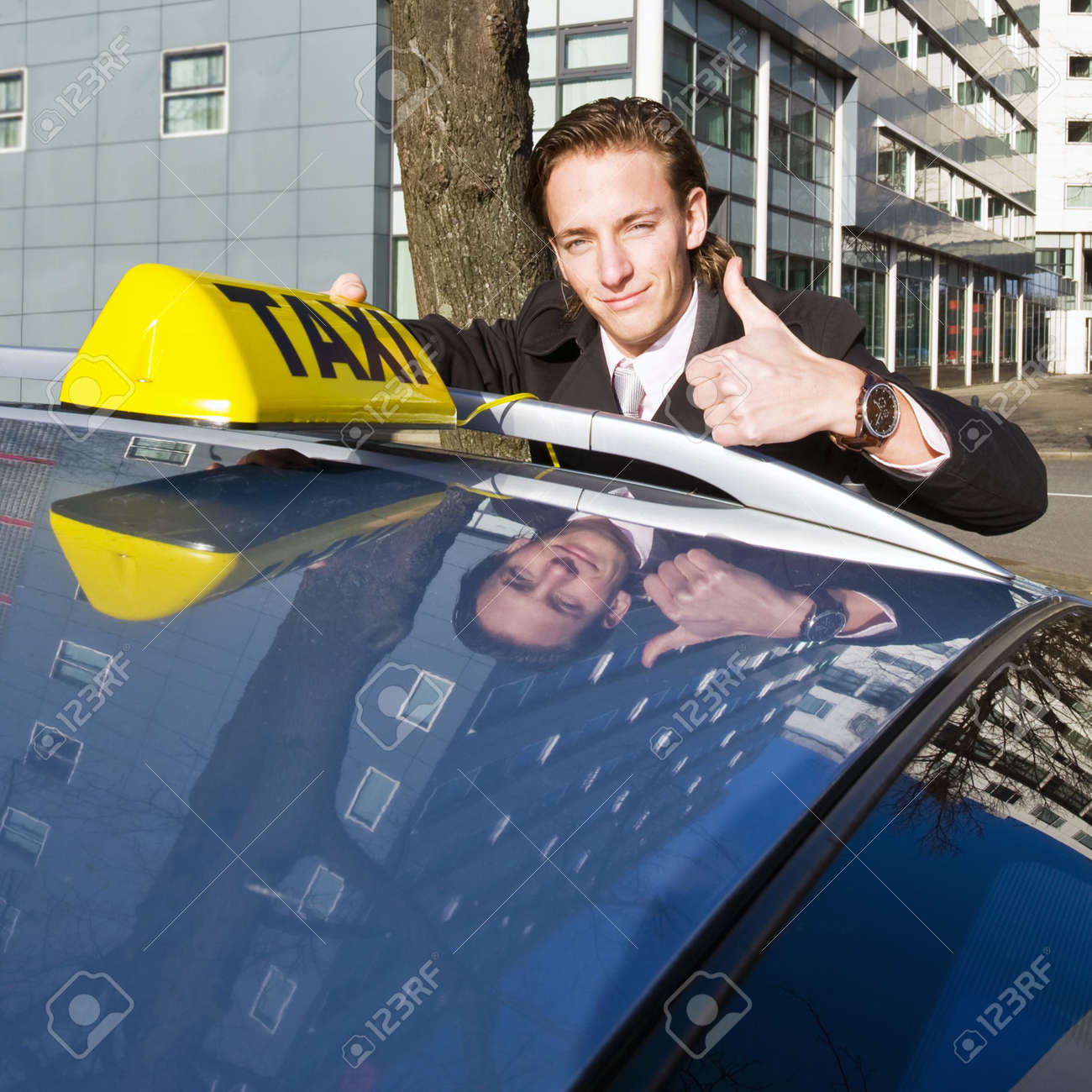 A smiling taxi driver giving a thumbs up while placing his taxi sign on the roof of his car Stock Photo - 6494276