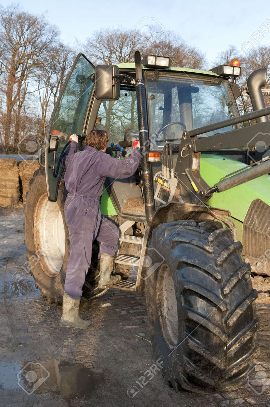 Farm hand boarding a big tractor Stock Photo - 6552700