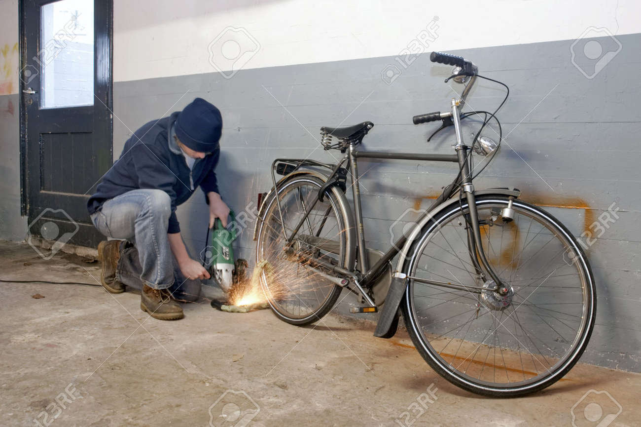 Bicycle thief busy breaking the lock with a portable grinding machine - 6552729