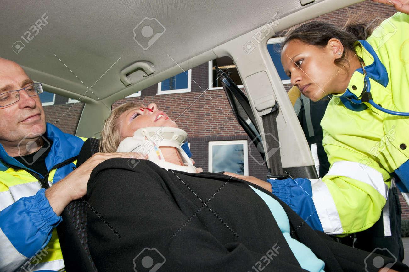 Paramedics placing a neck brace on an injured woman inside her car after a car crash Stock Photo - 7846302