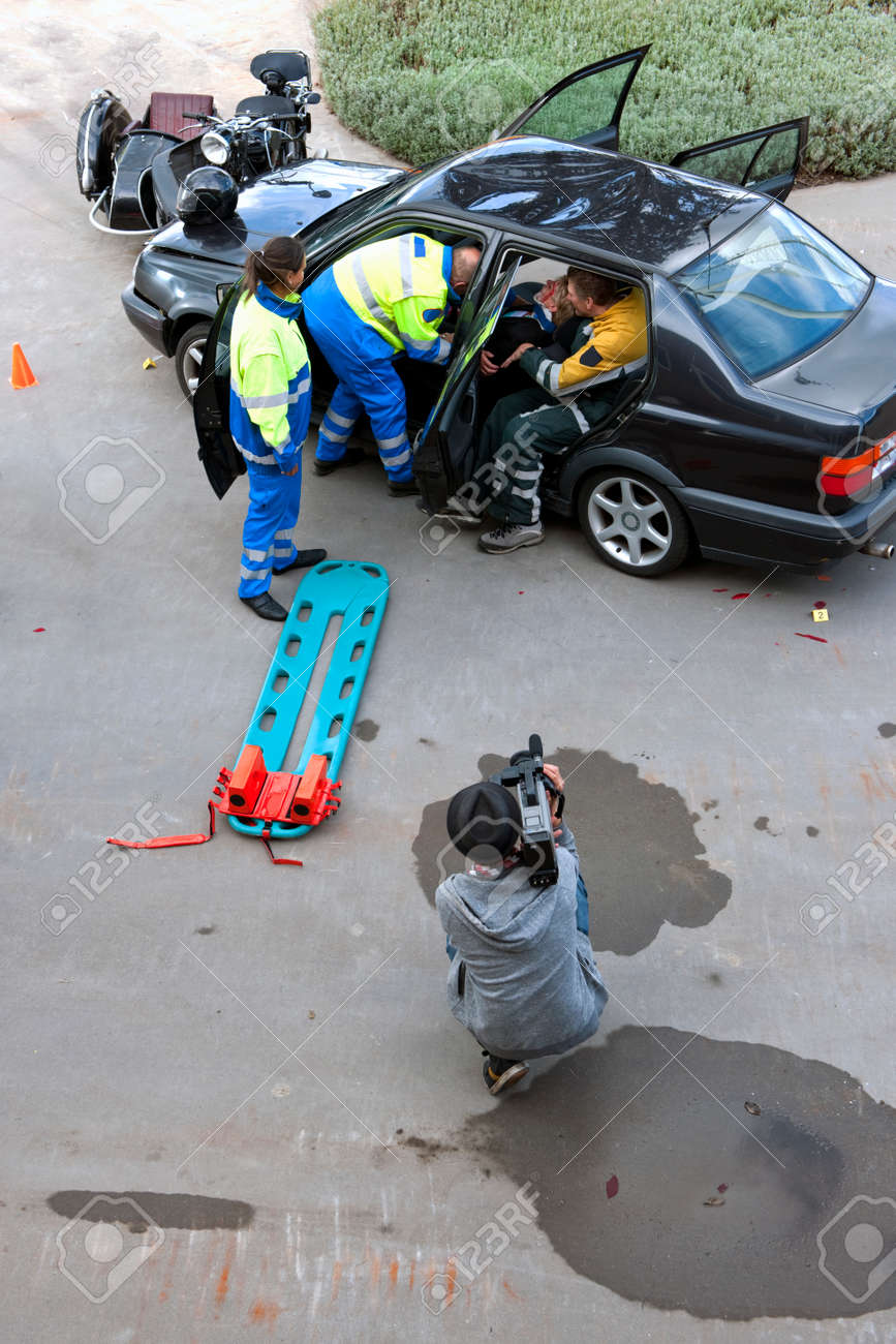 Emergency medical services team rescueing a wounded woman with neck injury from her damaged car after an accident, with the press present at a distance Stock Photo - 7846279