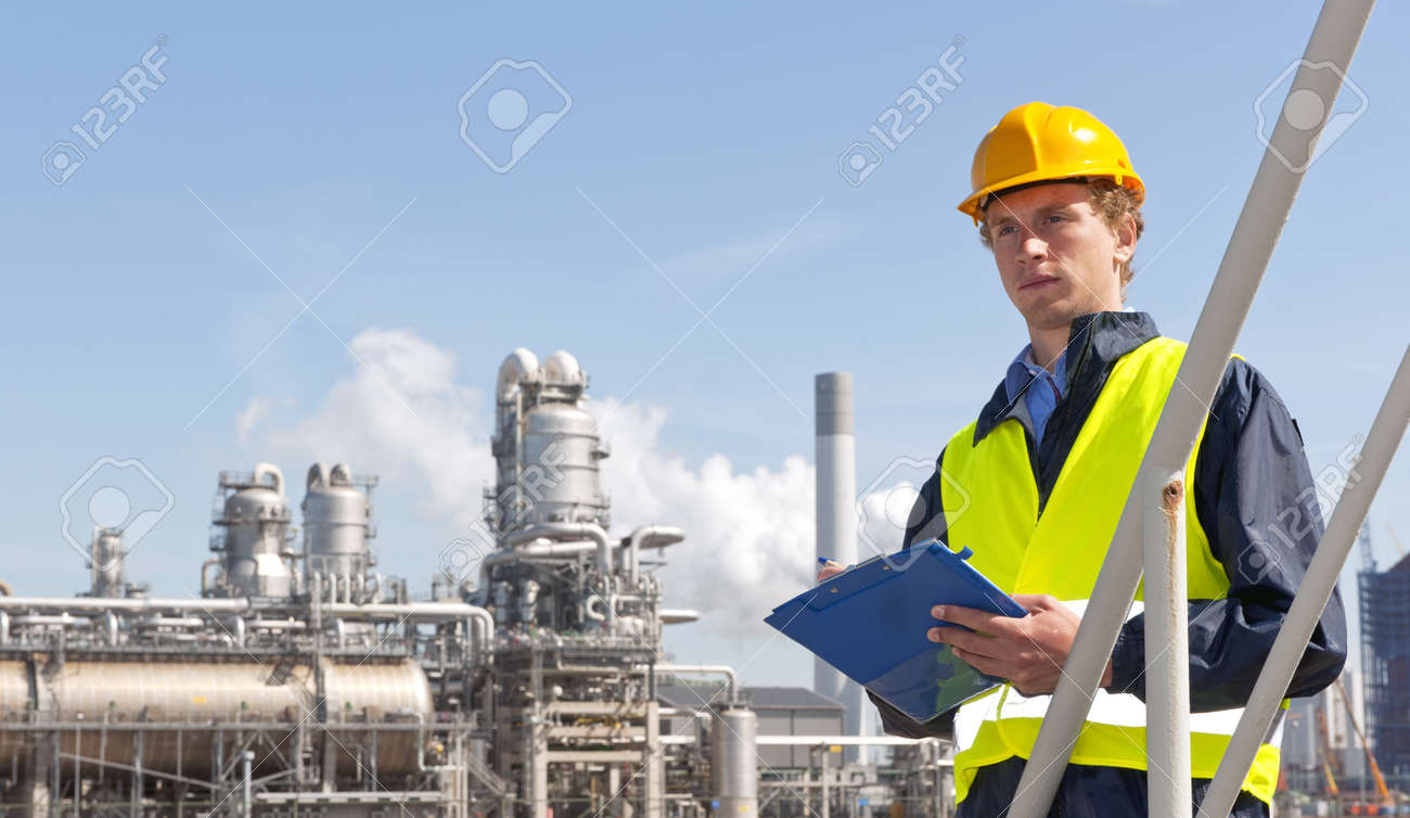 Young supervisor with a note board and pen in his hands, wearing a hard hat and safety vest in front of a petrochemical plant and refinery Stock Photo - 9636453
