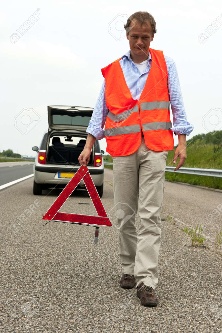 Man walking backwards from his car wearing a safety vest, carying a warning triangle Stock Photo - 10097591