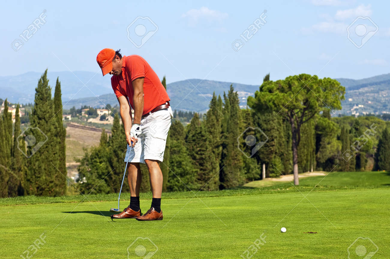 Golfer putting a ball on the green of a golf course Stock Photo - 10877573