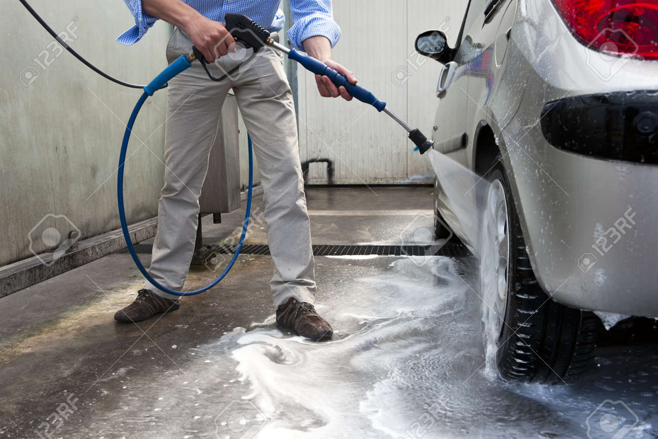 Man, wahsing his car in the stall of a car wash, using a high pressure water jet Stock Photo - 11864389