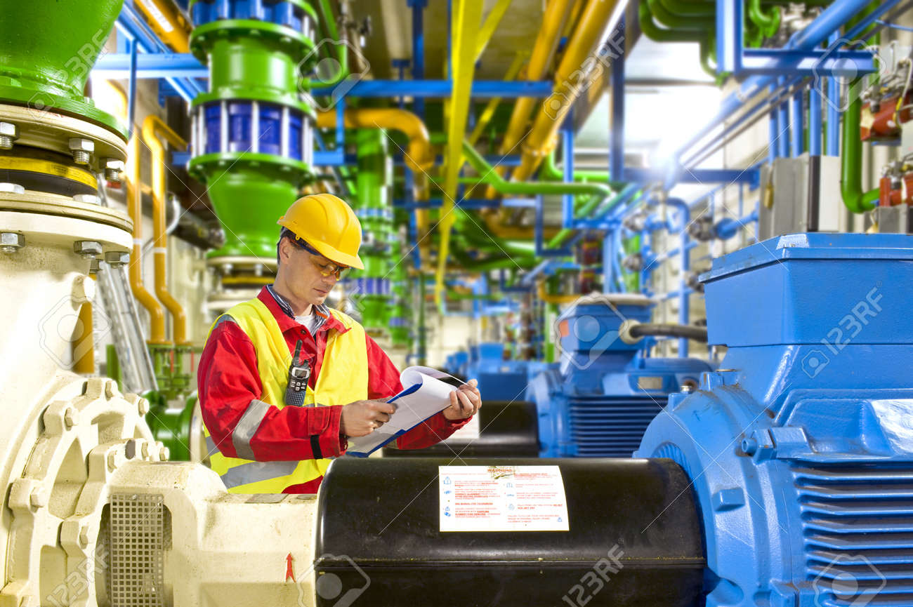 Engineer looking aty a checklist during maintenance work in a large industrial engine room Stock Photo - 13903778