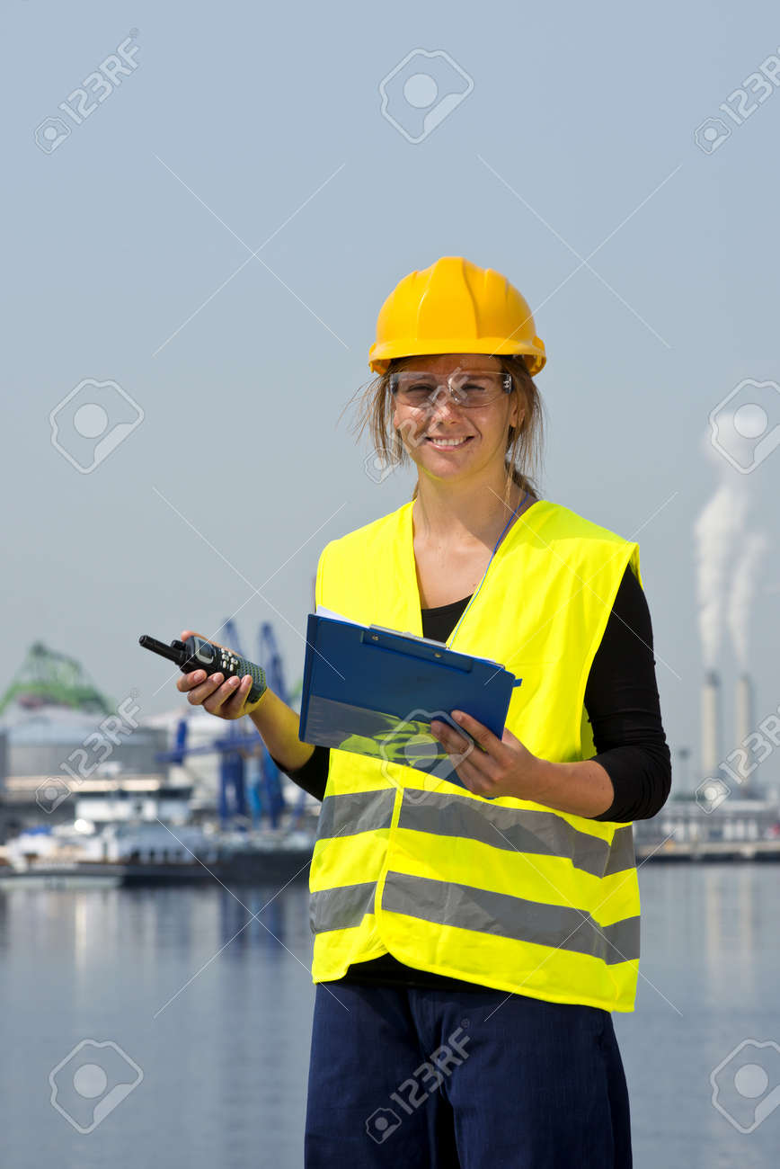 Smiling female docker with a clipboard and CB-radio on the waterfront of an industrial harbor Stock Photo - 14645584