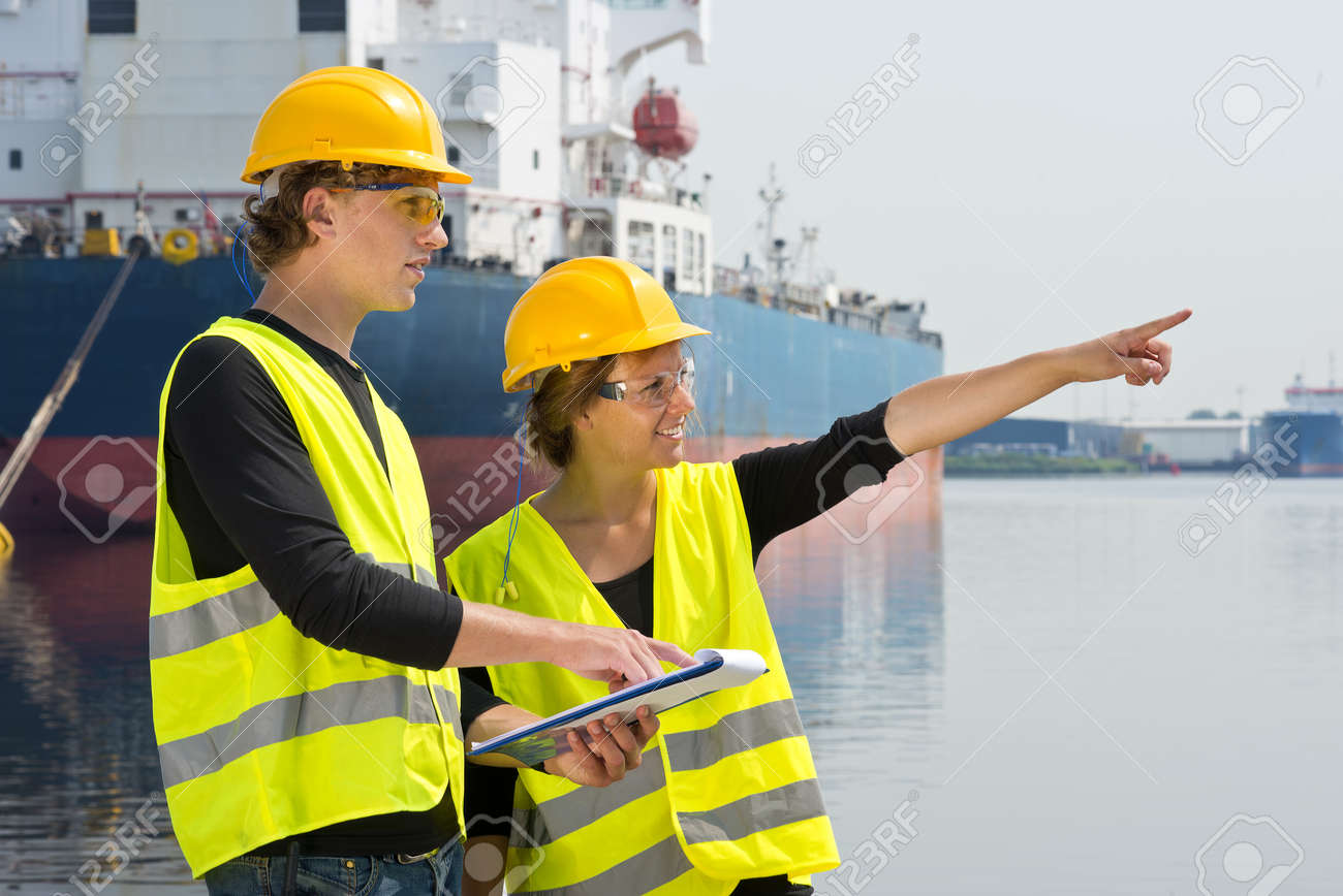 Two industrial engineers in a harbor, checking a plan from a clipboard on location Stock Photo - 14645588