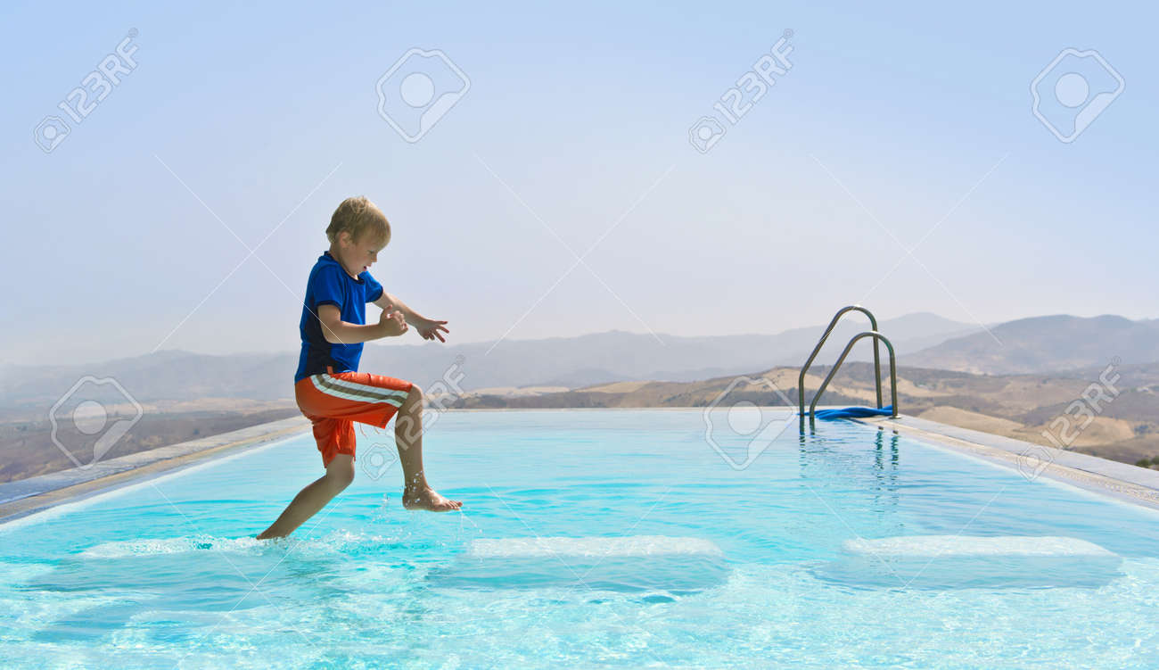 Boy Playing In a Swimming Pool, hopping from stepping stone to stepping stone Outdoors Stock Photo - 15045019