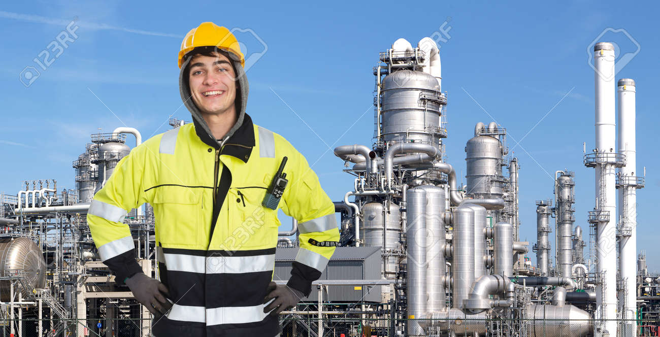 Happy, proud and confident chemical engineer smiling into the camera in front of a petrochemical plabnt, with stainless steel crackers, destillation towers, and a couple of smoke stacks in the background Stock Photo - 17382749