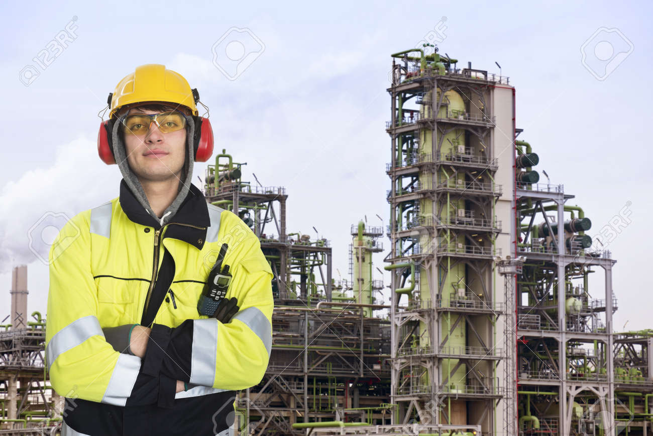 Young chemical engineer posing in front of a biodiesel refinary plant, wearing a hard hat, fire retardant clothing with reflective stripes, looking proudly into the camera Stock Photo - 17382745