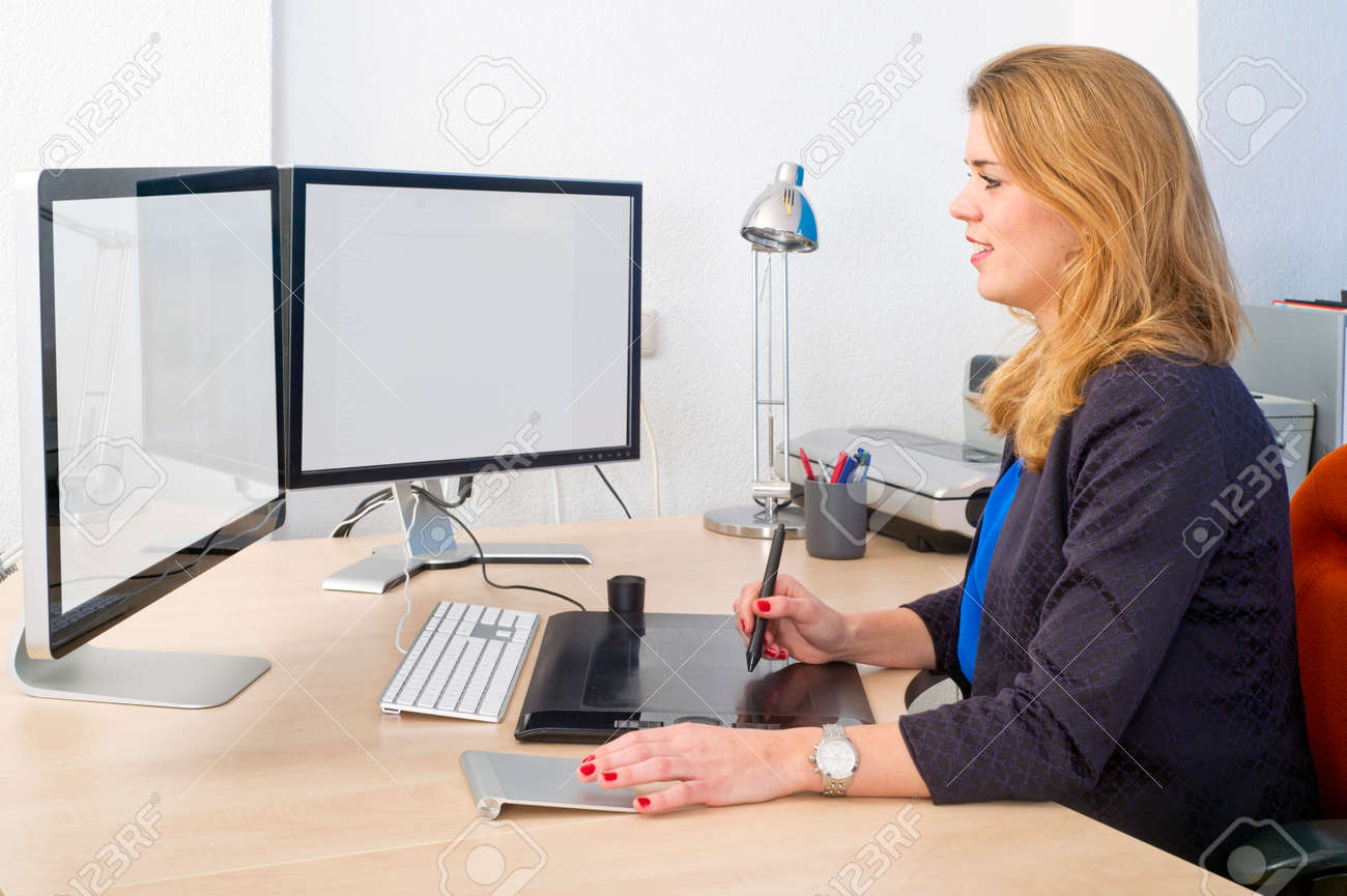 young woman sitting behind a large desk and a dual screen computer