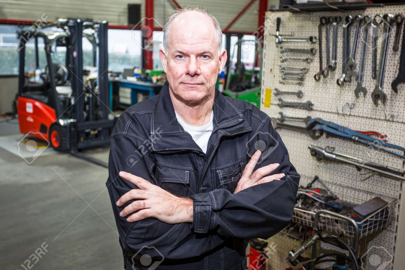 Forklift Mechanic Stands Confident In The Garage With A Wall - Forklift mechanic