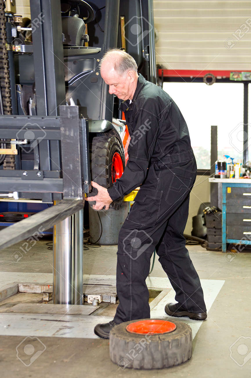 Forklift Mechanic Replacing A Front Tyre On A Forklift In A - Forklift mechanic