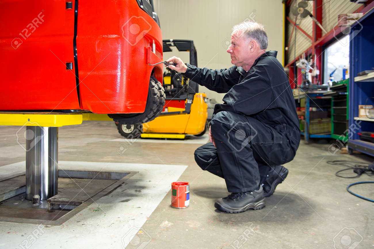 Mechanic Repainting A Forklift On A Bridge In A Workshop Stock - Forklift mechanic