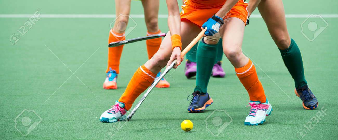 Field hockey players challenge eachother for possession of the ball on the midfield battle of a hockey mach Standard-Bild - 33153433