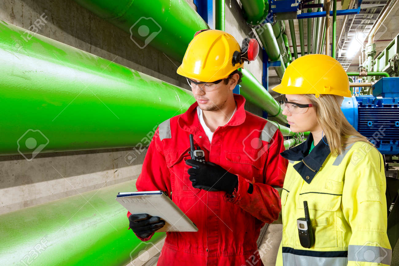 two maintenance engineers going through a checklist during a routine inspection of an industrial installation in a factory Standard-Bild - 34020871