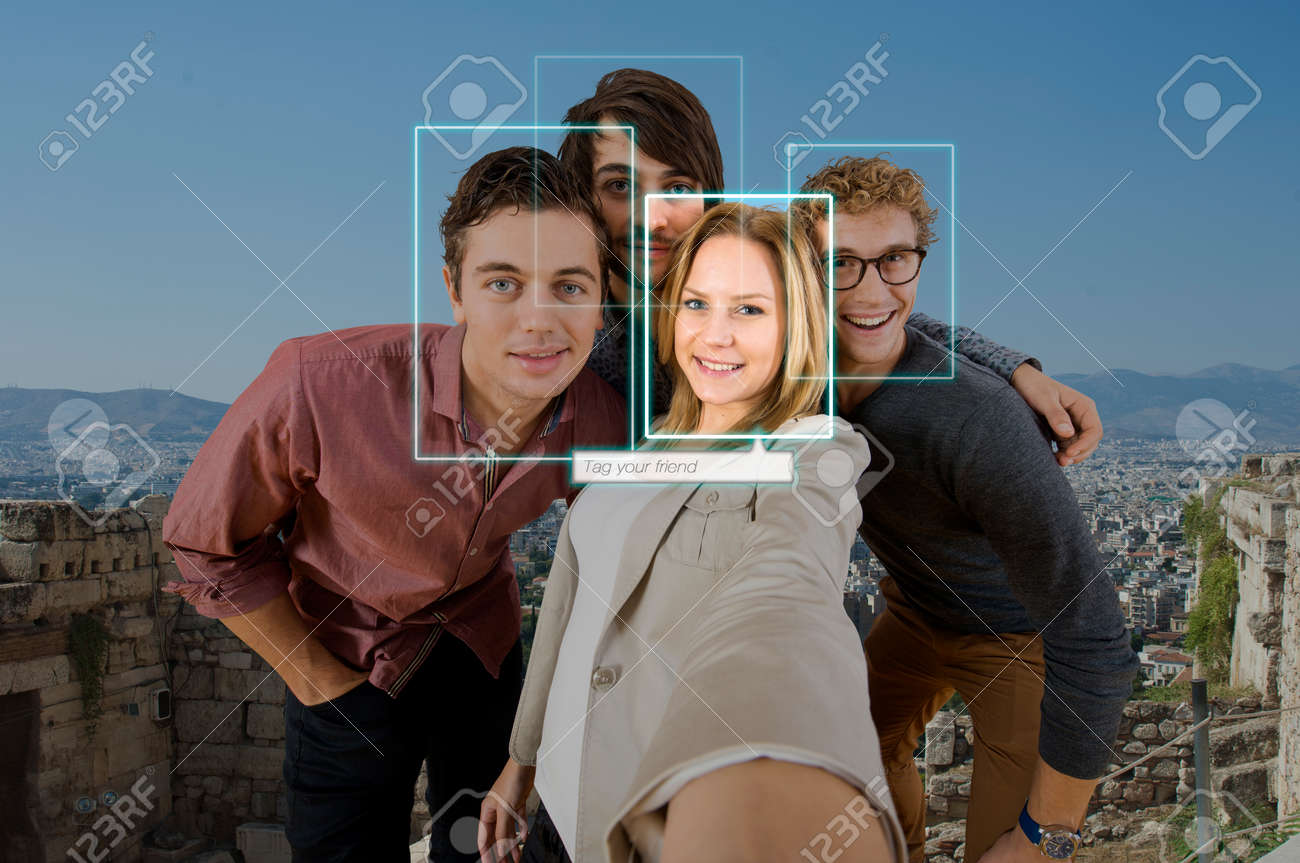 Tagging and sharing a friend in a selfie of four people using facial recogintion software applications in front of a large city for sharing on varous social media platforms Standard-Bild - 34020879