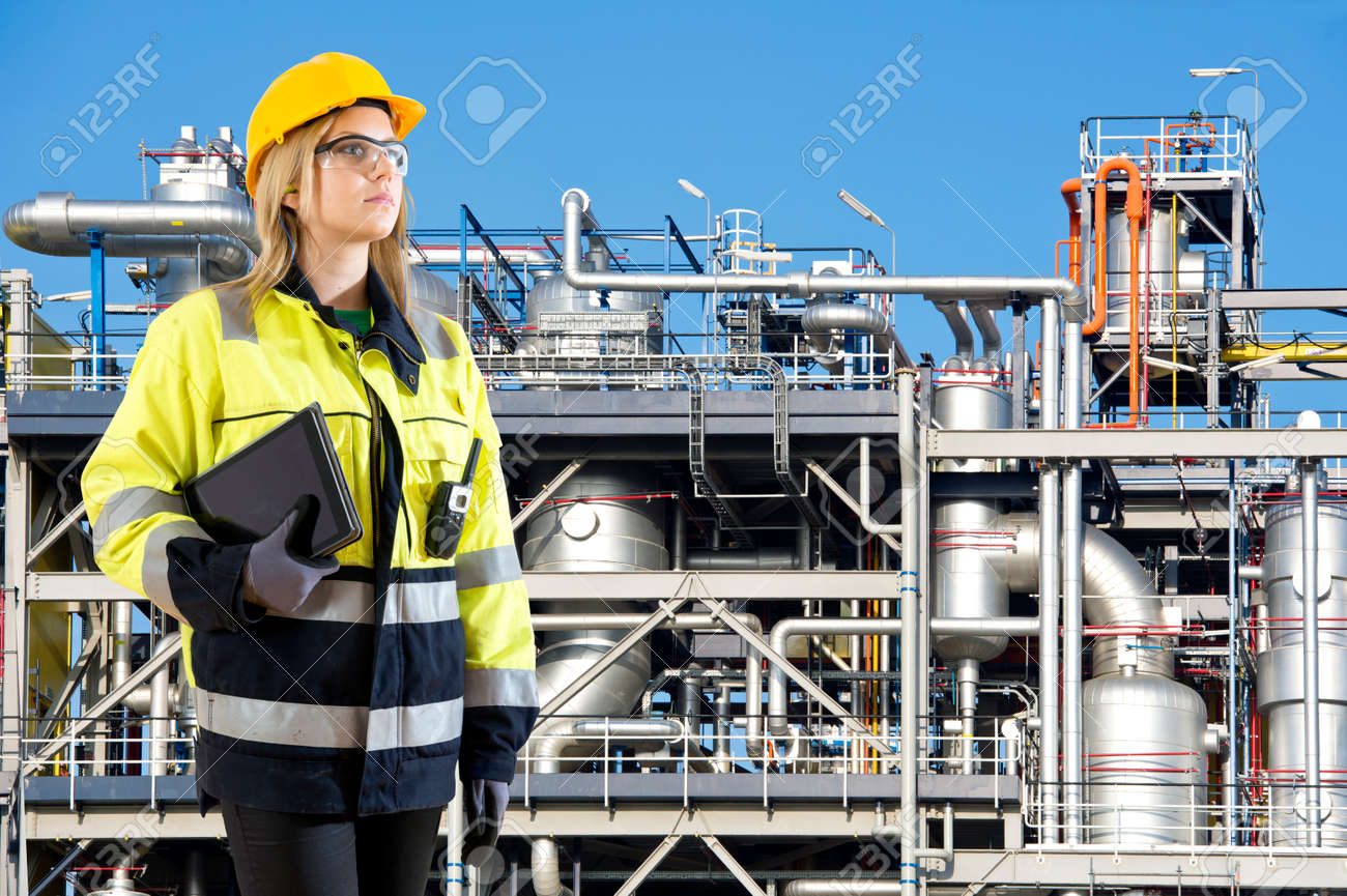 Woman, posing with a tablet and cb radio in front of a petrochemical installation as plant and safety officer Standard-Bild - 34323679