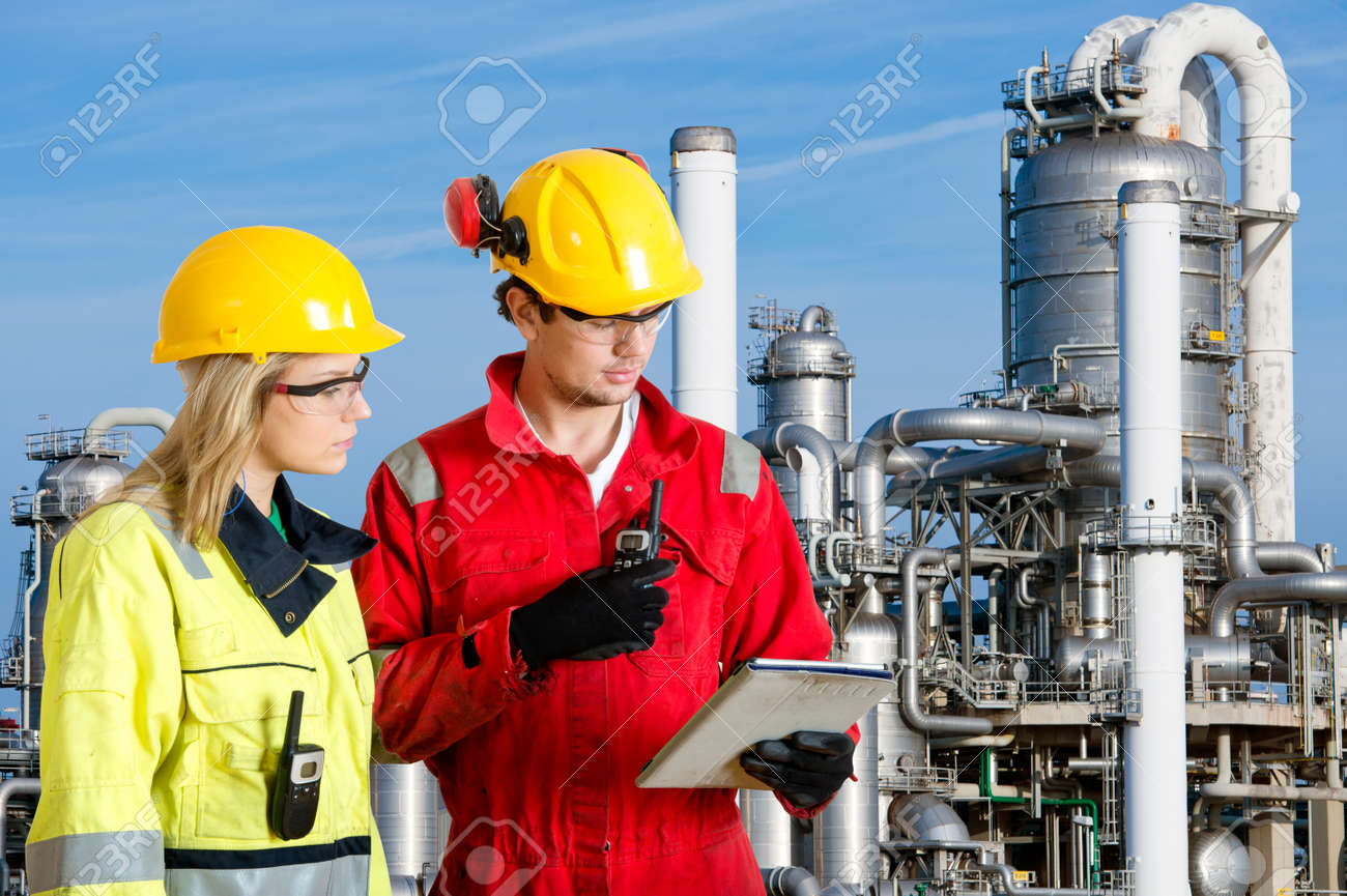 Two engineers going through routine checks, working at a petrochemical oil refinery using cb radios and a tablet computer Standard-Bild - 34323767