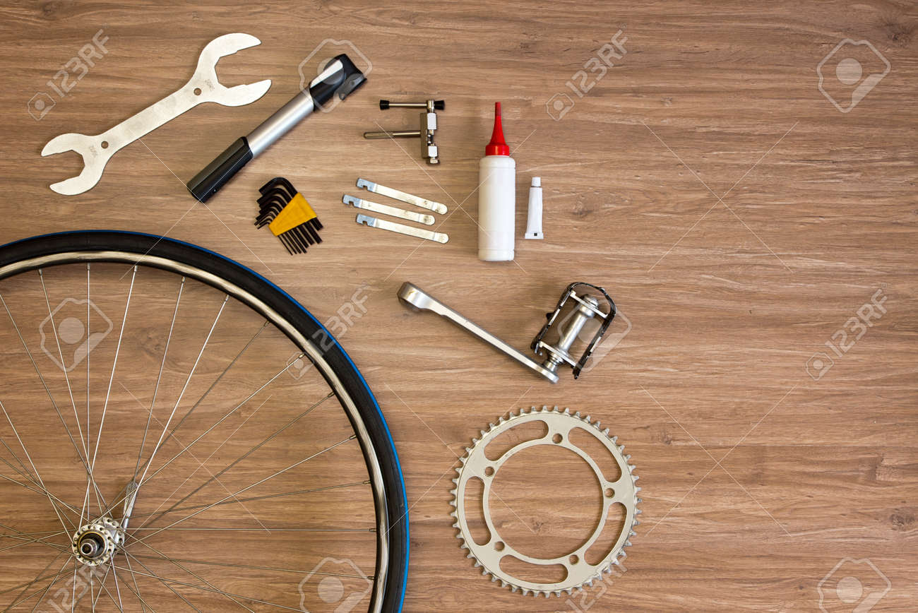 Assorted items, related with bicycle repair on a wooden background Standard-Bild - 34789569