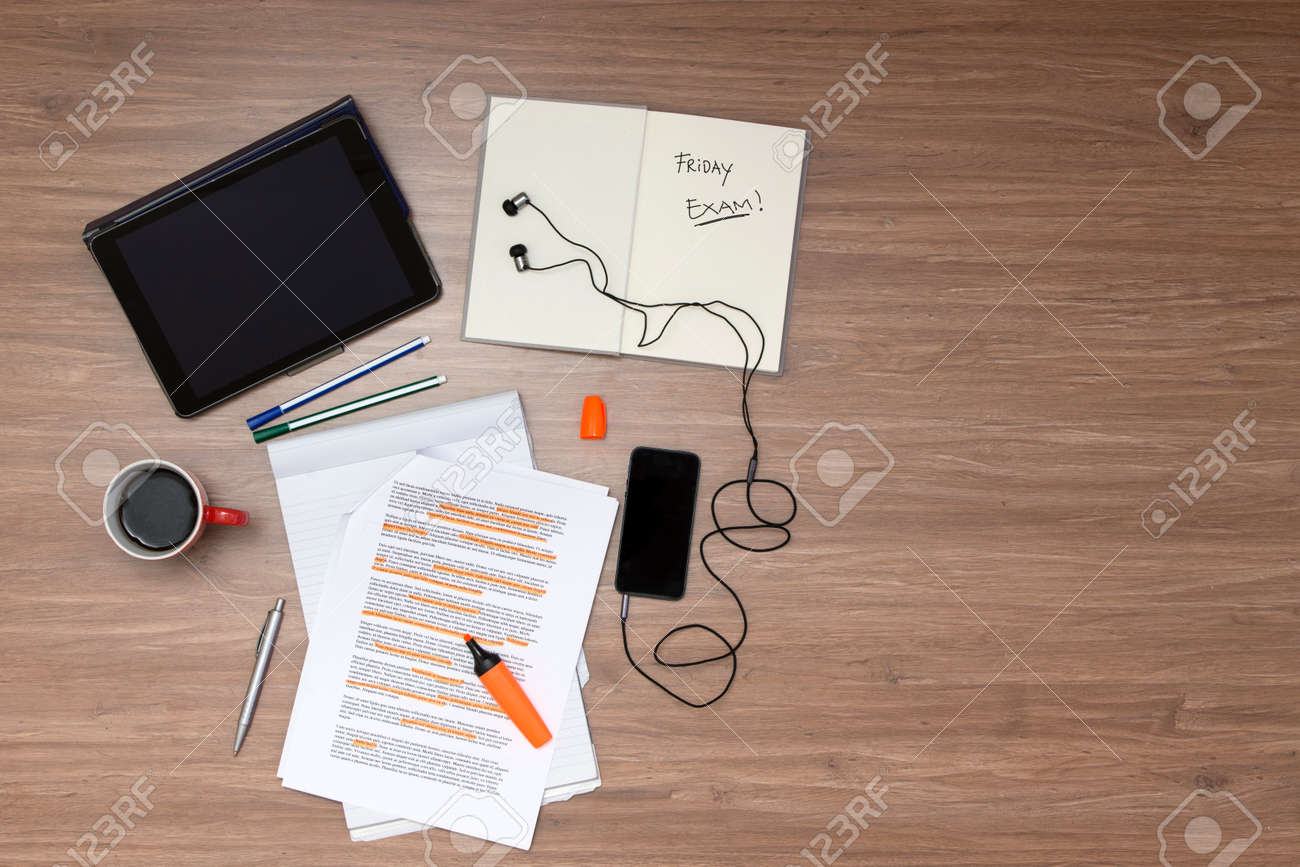 Background, filled with studying materials and copy space on a wooden surface. Items include an electronic tablet, music player, text book, cup of coffee, pens, markers, a high lighted standard (lorum ipsum) text, seen from above Standard-Bild - 34789750