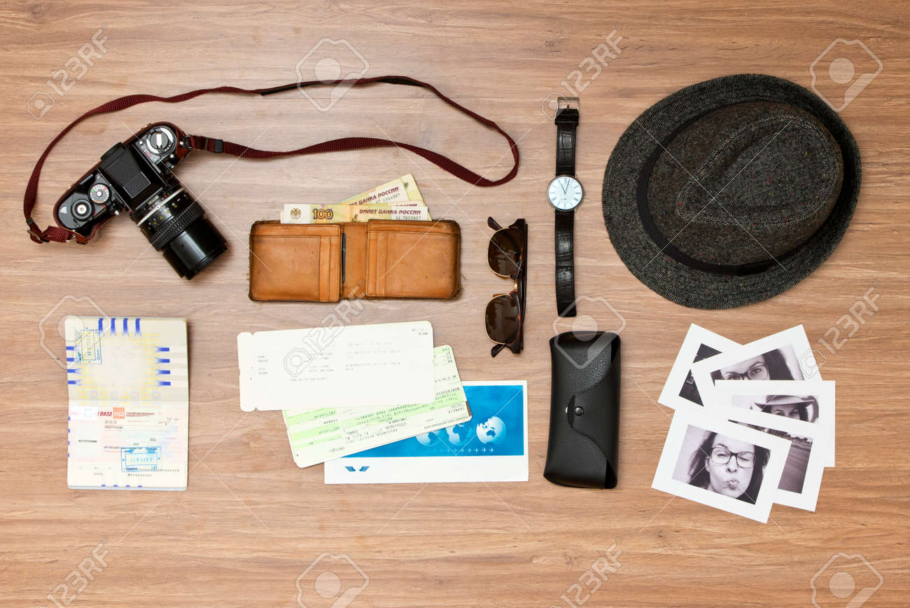 International travel background with a retro or vintage touch. Items include an old photo camera, passport, wallet with foreign currency, airplane ticket, hat, sunglasses and a couple of black and white photos Standard-Bild - 34832236