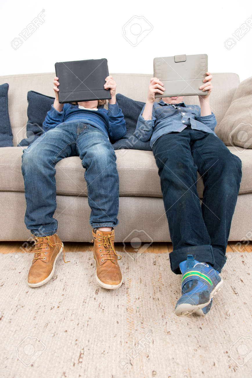 Two boys, slouching on a couch in a living room, each plaing games on a tablet computer. Standard-Bild - 35201659