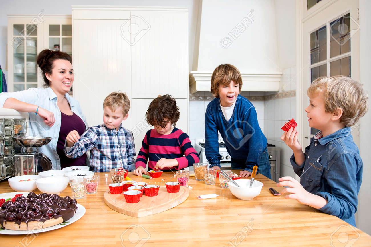 Boys and girls decorating cupcakes at a kitchen counter during a baking workshop for kids at a birthday party Standard-Bild - 35201671