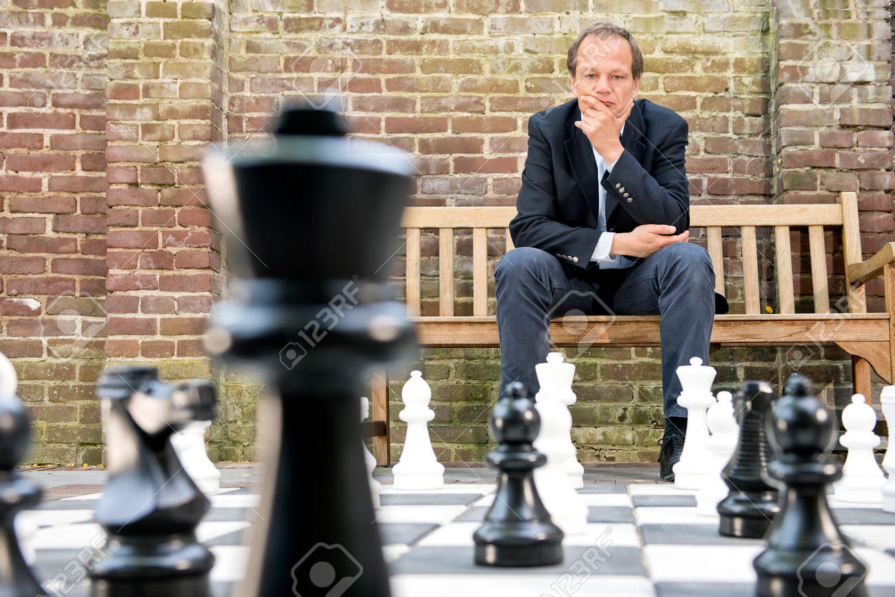 Concentrated man, thinking strategically about his next move, sitting on a wooden bench in front of a brick wall during an outdoor chess game using life sized chess pieces and chess board - 41411270
