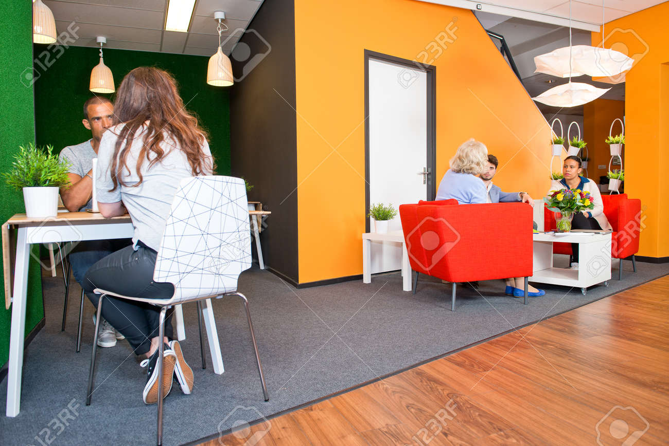 Lobby and multi-purpose waiting area, with several groups of people sitting at tables during informal meetings of a modern styled office Standard-Bild - 41781852