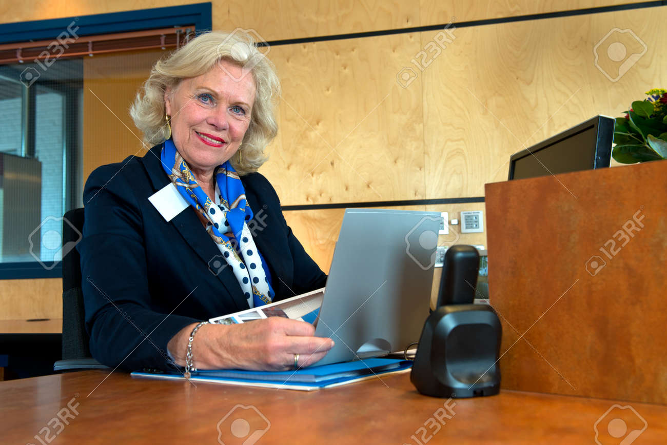 smiling senior receptionist sitting at the front desk as an smiling senior receptionist sitting at the front desk as an example of successful reintegration after retirement