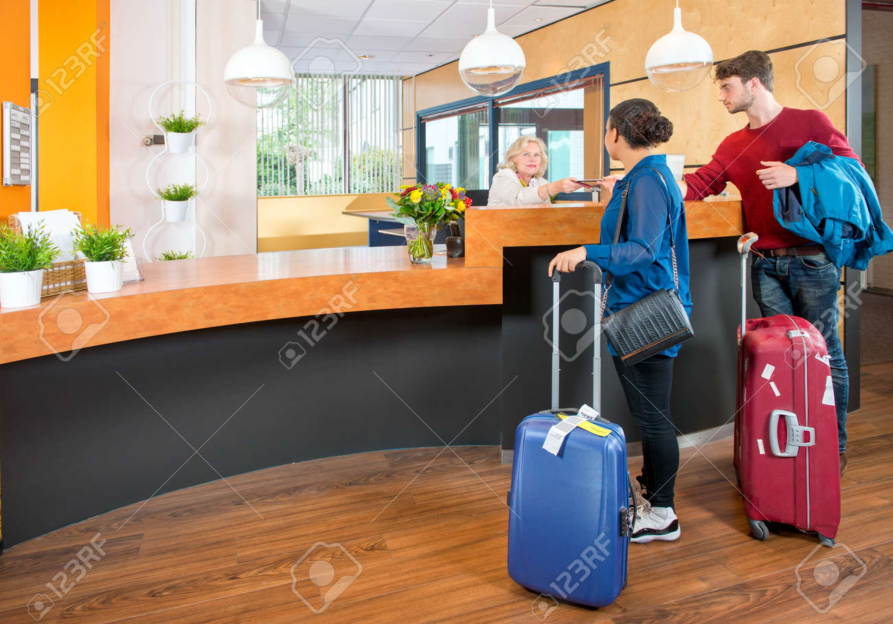 Young couple at the check in counter of a hotel,having just arrived with their luggage from the airport Standard-Bild - 41781856
