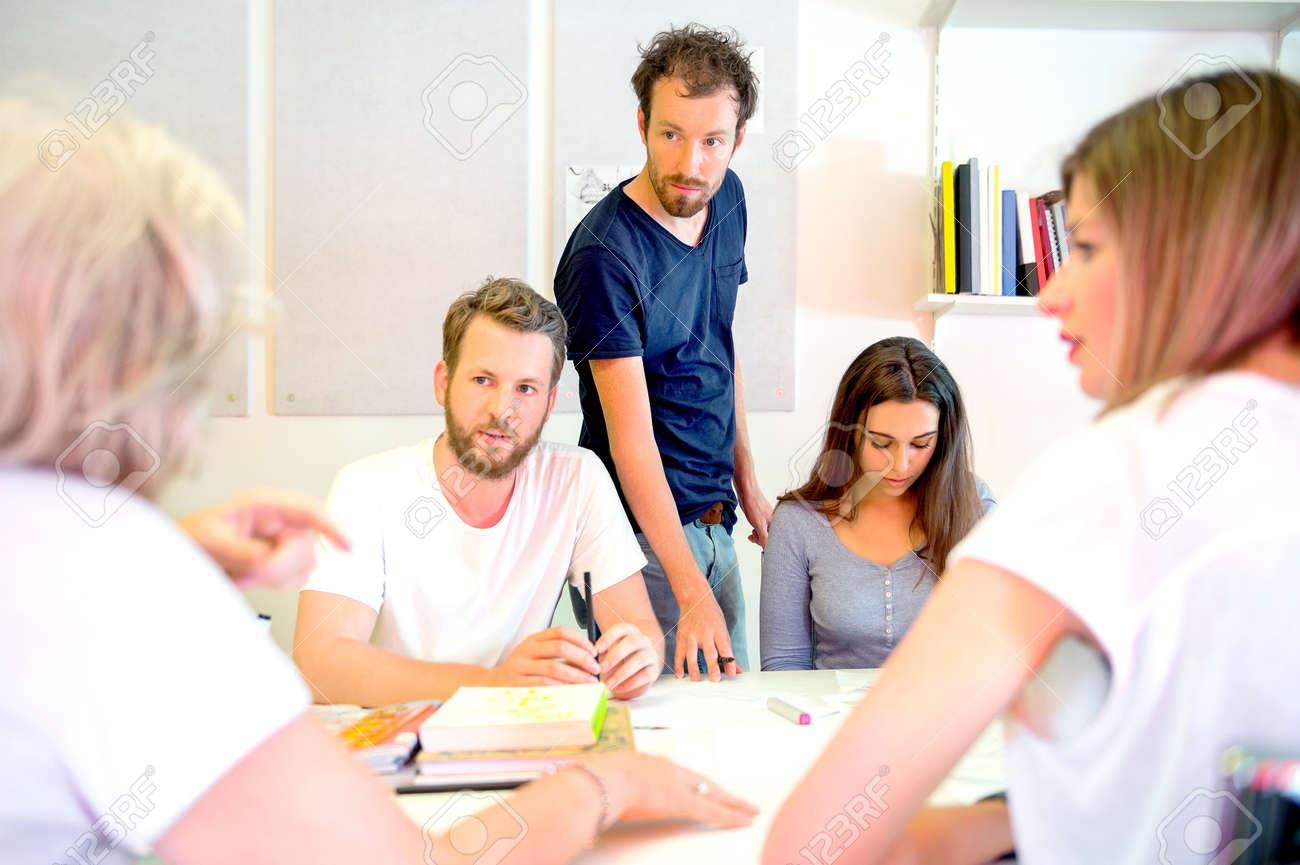 Team of male and female 3D designers discussing at desk in printing studio Standard-Bild - 43472098