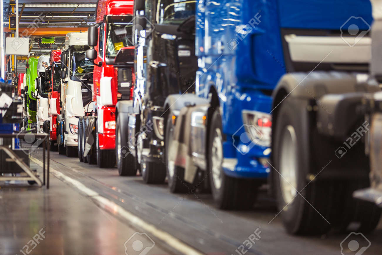 Row of brand new, shiny, trucks in various colours, ready to come off a production line in a truck factory Standard-Bild - 45171007
