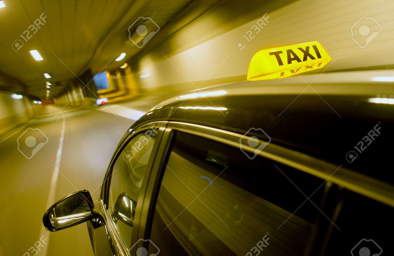 A black taxi, driving through a dunnel, with the taxi sign lit, apporaching a junction and exit ramp Standard-Bild - 45354337