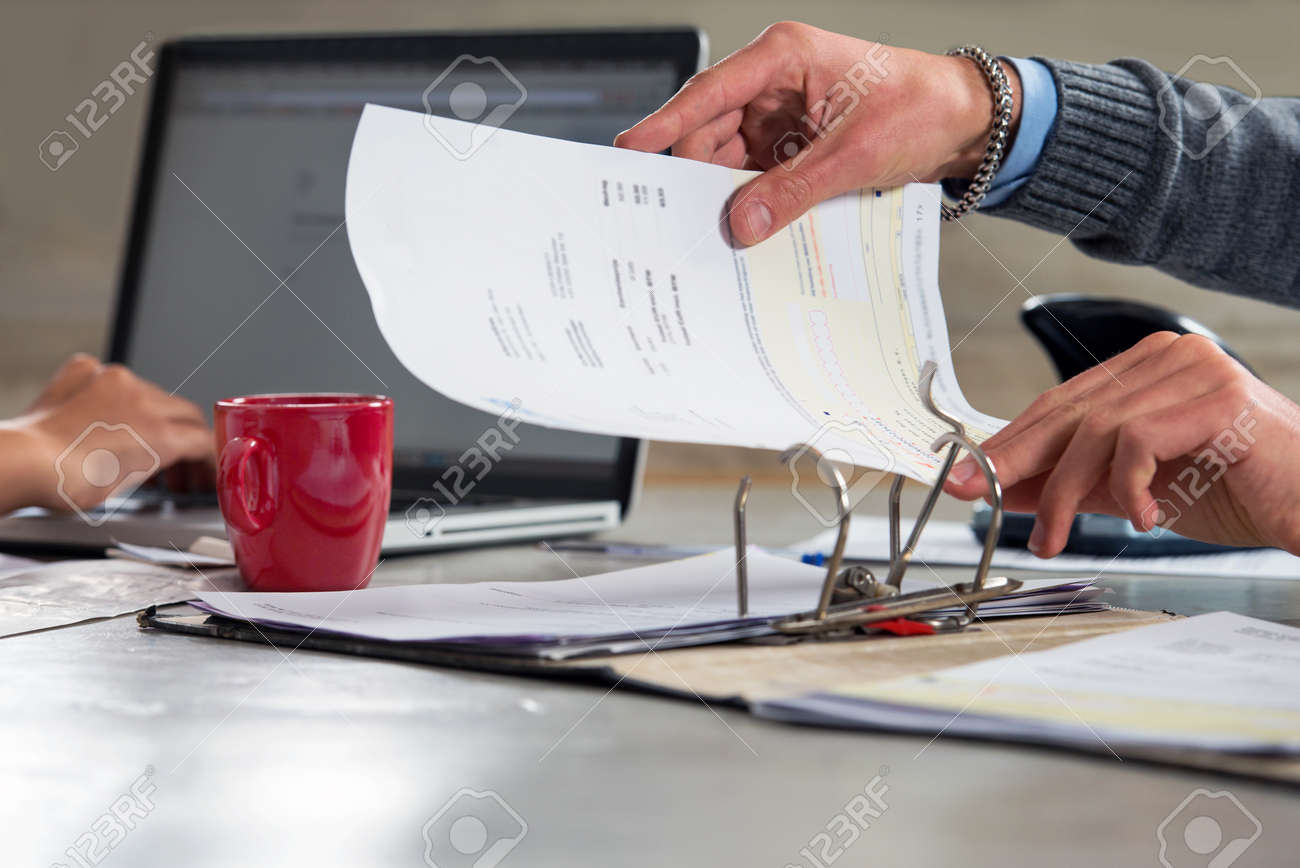 People, fining documents and doing their administration, working on a laptop and filing invoices and bills in a ring binder, archiving them for tax returns Standard-Bild - 47655918