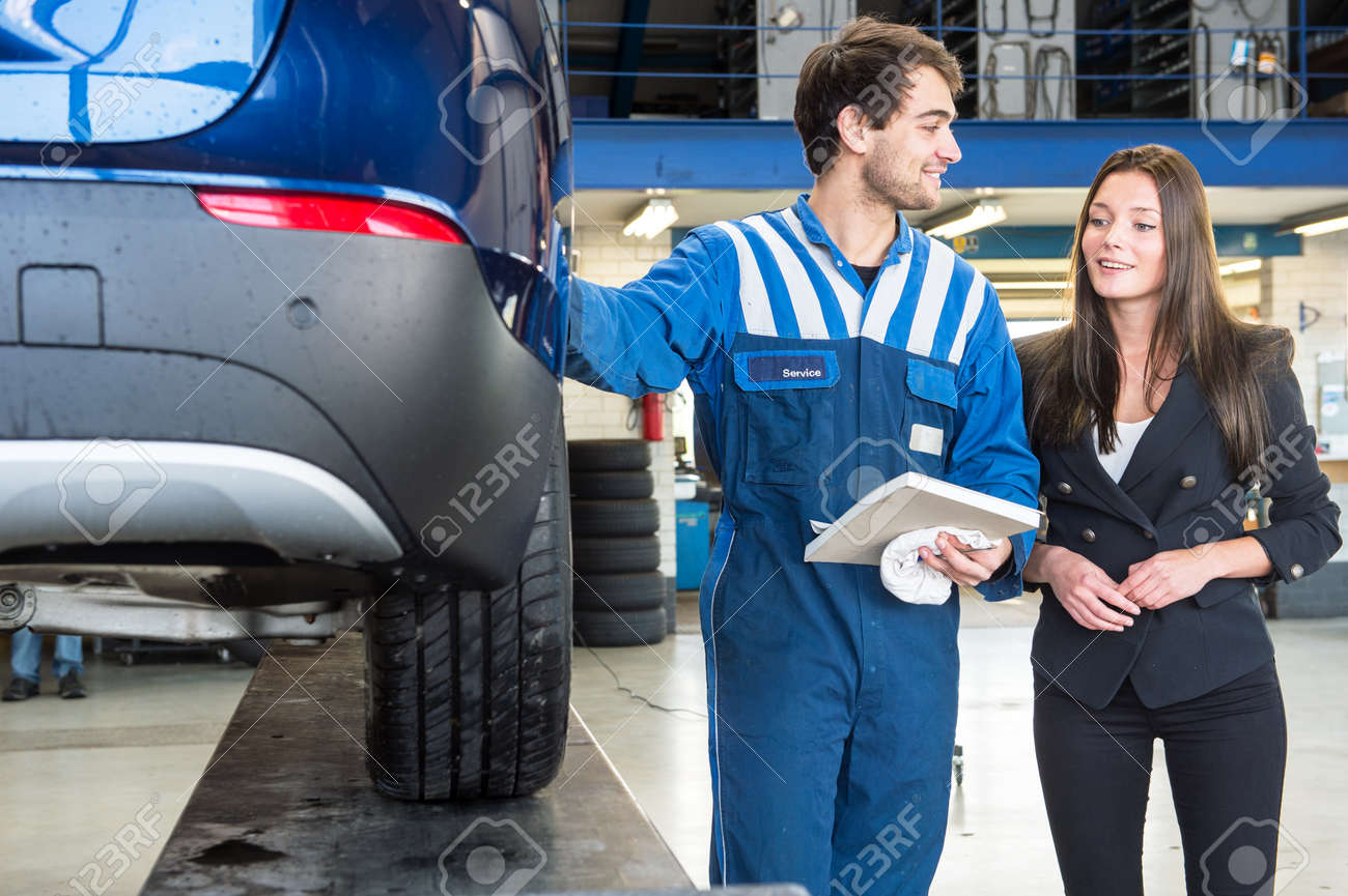 A friendly mechanic providing customer service to a young business woman, showing her the work he's done on her car, equipped with a new set of winter tires to ensure road safety. Standard-Bild - 47426057