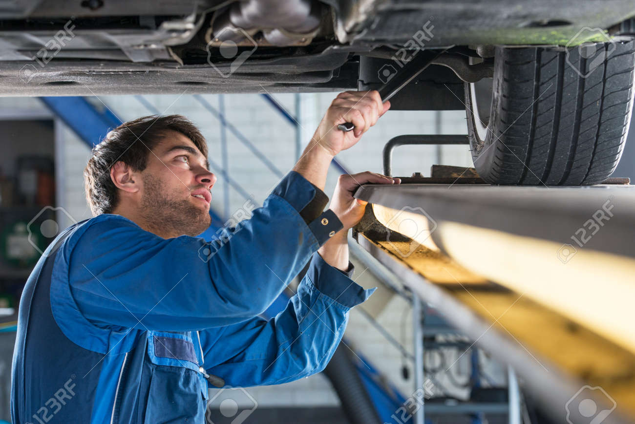 Mechanic, examining the suspension of a vehicle with a steel rod for any undesired clearances as part of a periodical vehicle safety inspection or mot test Standard-Bild - 47426255