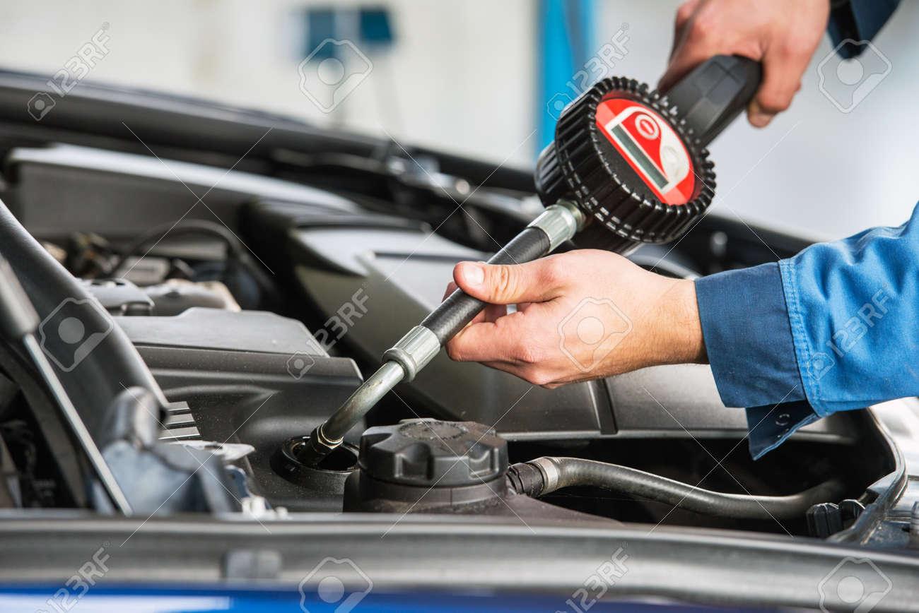 A modern sedan gets an oil change by a mechanic, using an electronic dosage system. Standard-Bild - 47558145