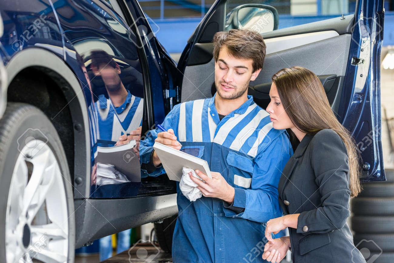 Car mechanic with female customer going through maintenance checklist in garage Standard-Bild - 47728184
