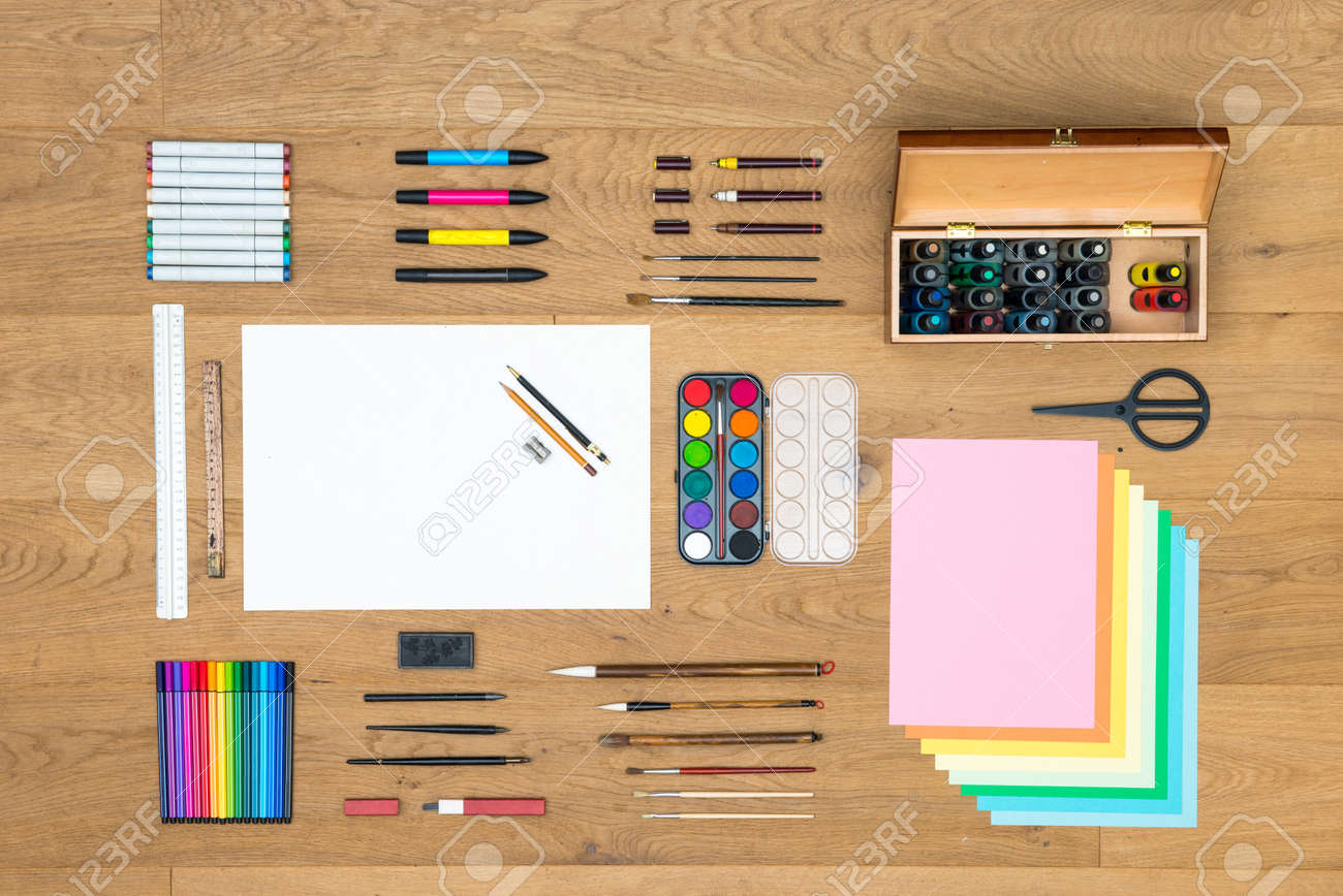 Assorted array of arts, crafts, drawing and design items, such as pens, rulers, markers, felt tip pens, fountain pens brushes, watercolor, and various sheets of paper on a wooden surface Standard-Bild - 48989201