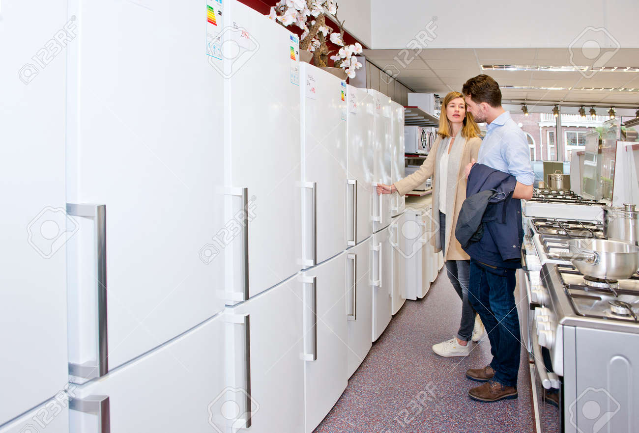Young couple shopping for a new refrigirator in an electronics and home appliance store with a broad selection of white goods Standard-Bild - 53858692