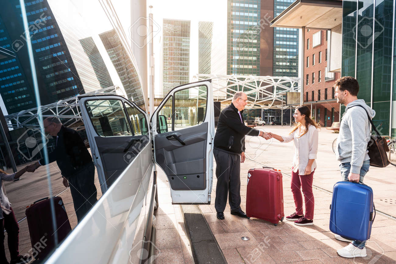 Driver of a airport shuttle minivan, greeting his passengers with their luggage on the sidewalk of a modern city business district Standard-Bild - 74738475