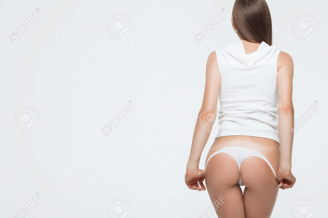 Crop back view of anonymous seductive female standing and removing thong - 105596037